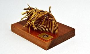 escultura para regalo corporativo hecha en bronce y madera que representa una ola