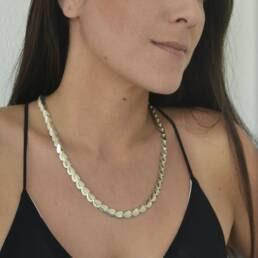 modelo con collar de plata que representa escamas de peces o reptiles