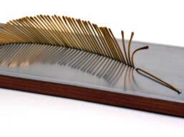escultura hecha en bronce, aluminio y madera, pluma