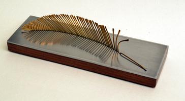 escultura para regalo corporativo que representa una pluma en bronce, madera y aluminio